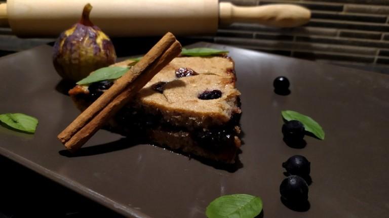 Κομμάτι Linzer torte, ένα στικ κανέλας, ένα σύκο, μερικά φραγκοστάφυλα και φύλλα βασιλικού σε καφέ ορθογώνιο πιάτο, και ένας ξύλινος πλάστης στο βάθος